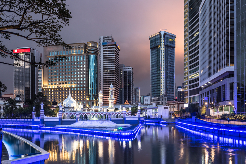 Office buildings reflect in the water of the Klang river in front of the Jamek mosque in Kuala Lumpur
