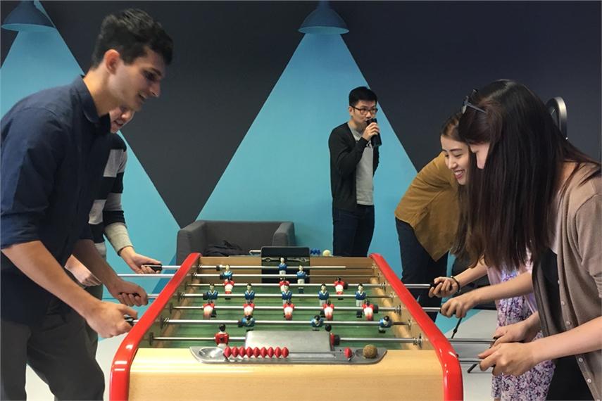 ゲーム室でテーブルサッカーゲームに興ずる、エッセンス シンガポールの社員