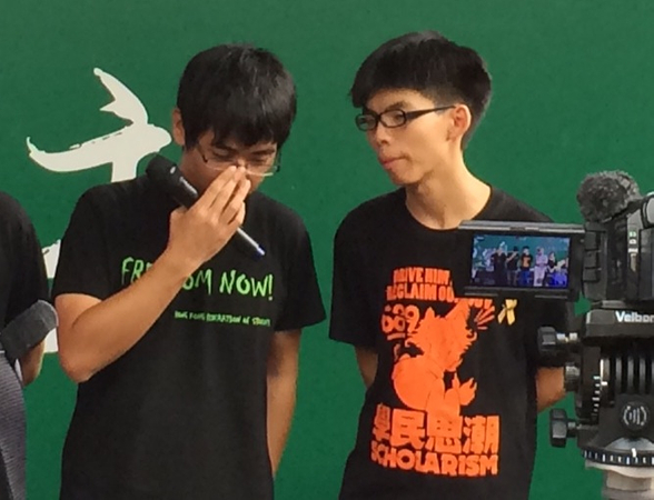 Alex Chow (left) confers with Joshua Wong on how to answer a question asked by a journalist