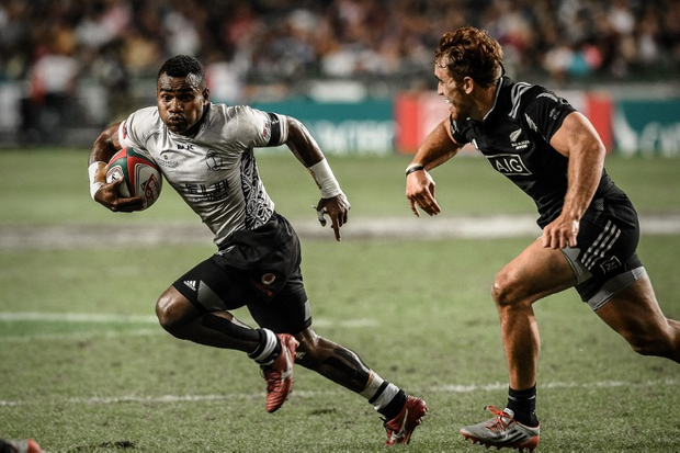 Fiji's Jerry Tuwai (L) runs away from New Zealand's Jo Webber during the final match between New Zealand and Fiji on the third and final day of the rugby sevens tournament in Hong Kong on March 29, 2015. Fiji won 33-19. AFP PHOTO / Philippe Lopez