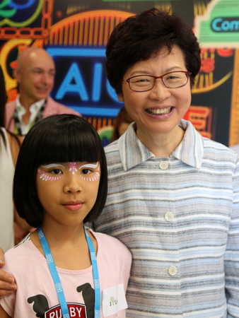 Hong Kong's chief executive-elect Carrie Lam greets a young visitor to the Mission Possible box