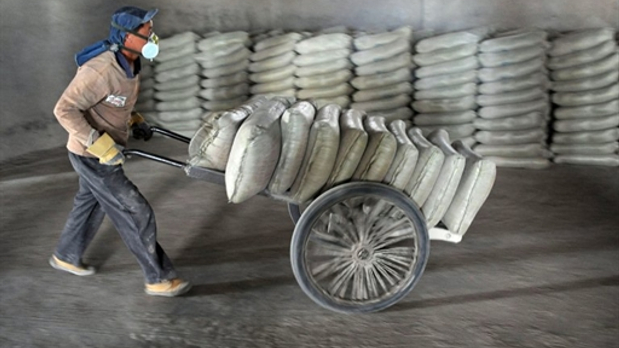 A worker delivers bags of cement to a Chinese factory.
