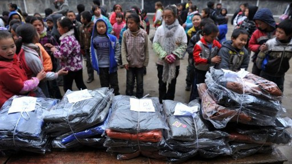 "<div style=""text-align: left;""> The have-nots: young students line up to get new winter clothes during a donation ceremony in Guizhou province (AFP) </div>"